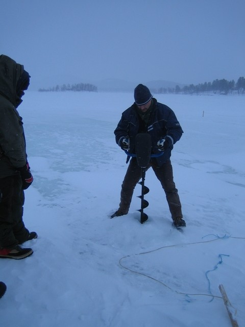 Peter creusant la glace pour l'ice-fishing